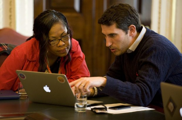 A man and a woman are looking at a laptop screen. The man is pointing at something on the screen