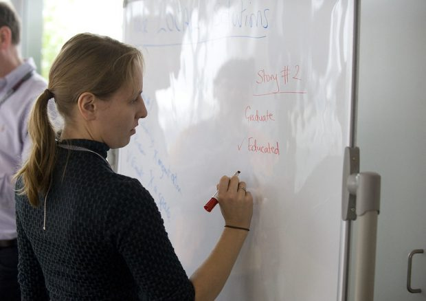 "A woman writes on a whiteboard: ""Story #2: Graduate, Educated (check mark)"""